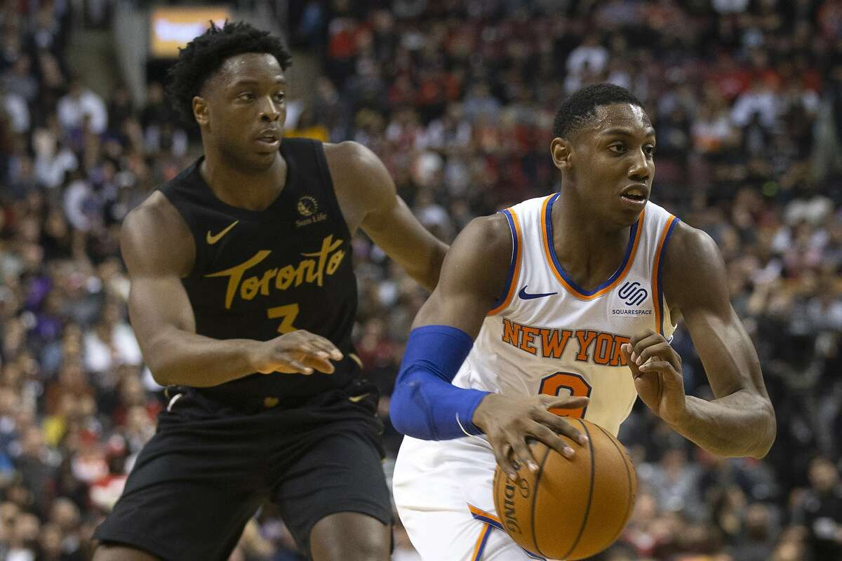 New York Knicks RJ Barrett, right, drives past Toronto Raptors OG Anunoby during second half of an NBA basketball game in Toronto on Wednesday Nov. 27, 2019. (Chris Young/The Canadian Press via AP)