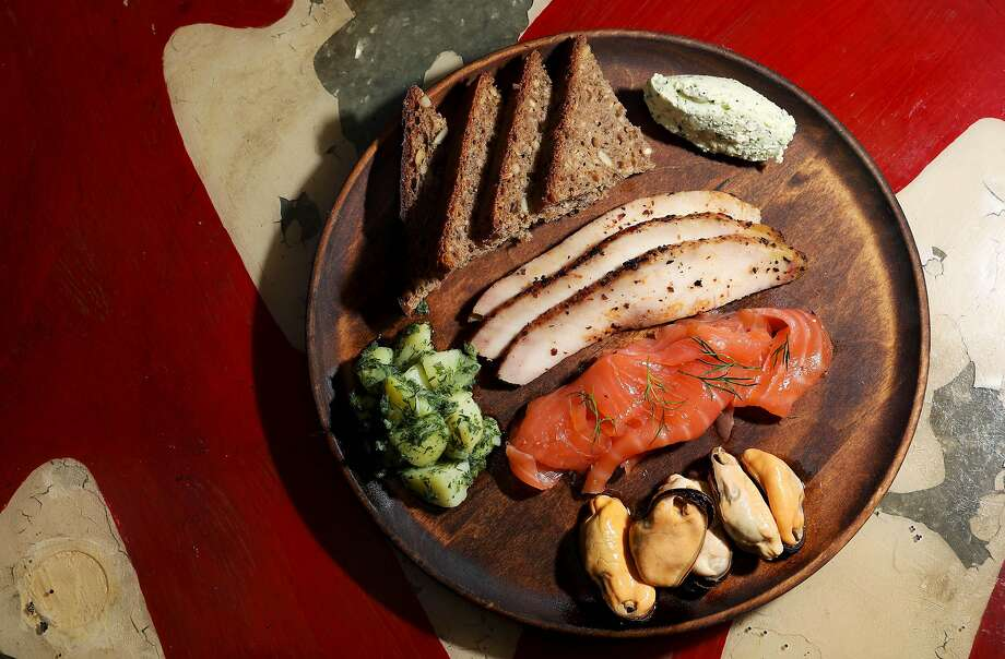 At Dear Inga in S.F., the smoked fish plate features smoked sturgeon, cured salmon, pickled mussels, farmer's cheese, German potato salad and seeded rye. Photo: Yalonda M. James / The Chronicle