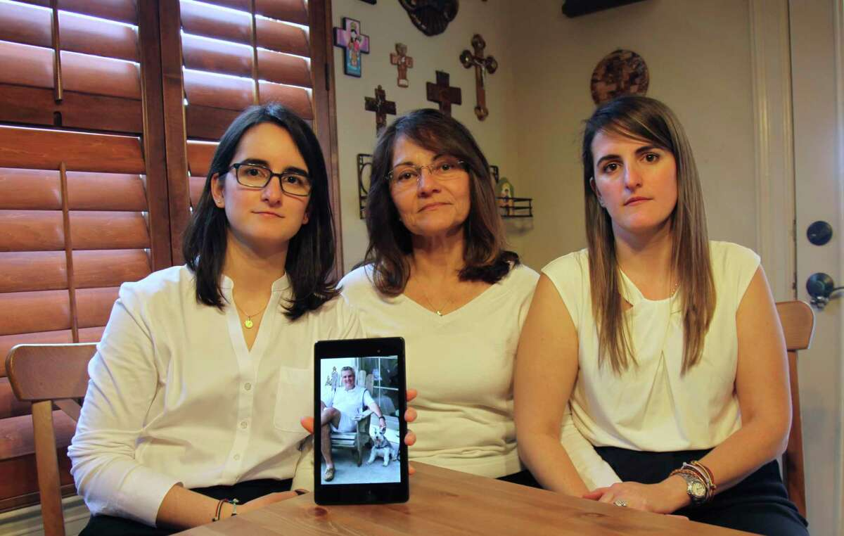 Dennysse Vadell sits between her daughters Veronica, right, and Cristina holding a digital photograph of father and husband Tomeu who is currently jailed in Venezuela, at their home in Katy, Texas, Friday, Feb. 15, 2019. Tomeu Vadell is one of six executives from Houston-based Citgo who has spent 15 months jailed in Venezuela on what their families say are trumped-up corruption charges. (AP Photo/John L Mone)