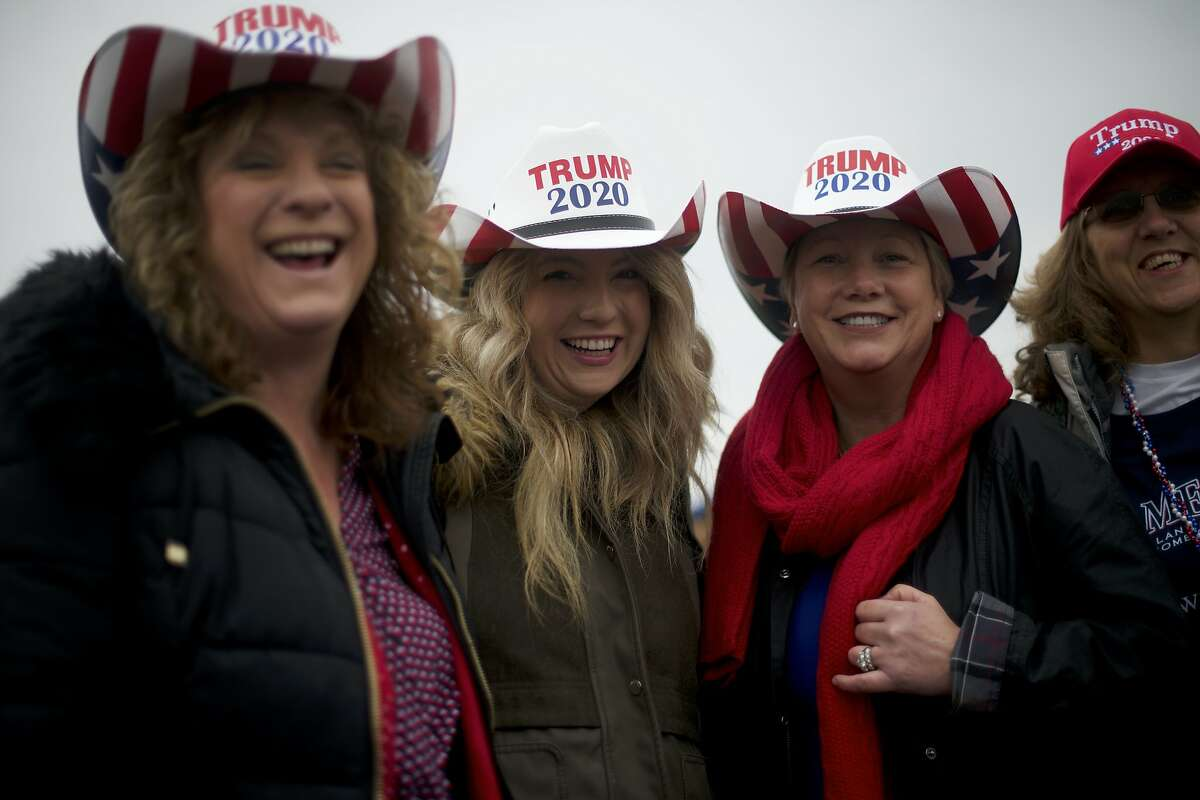 """HERSHEY, PA - DECEMBER 10: Trump supporters (L-R) Lisa Reed, Meredith Reed, Helen Williams, Michelle Weller wear cowboy hats stating """"TRUMP 2020"""" while waiting in the rain before U.S. President Donald J. Trump holds a campaign rally on December 10, 2019 in Hershey, Pennsylvania. This rally marks the third time President Trump has held a campaign rally at Giant Center. U.S. Vice President Mike Pence is also slated to attend, signifying the importance Pennsylvania holds as a key battleground state. (Photo by Mark Makela/Getty Images)"""