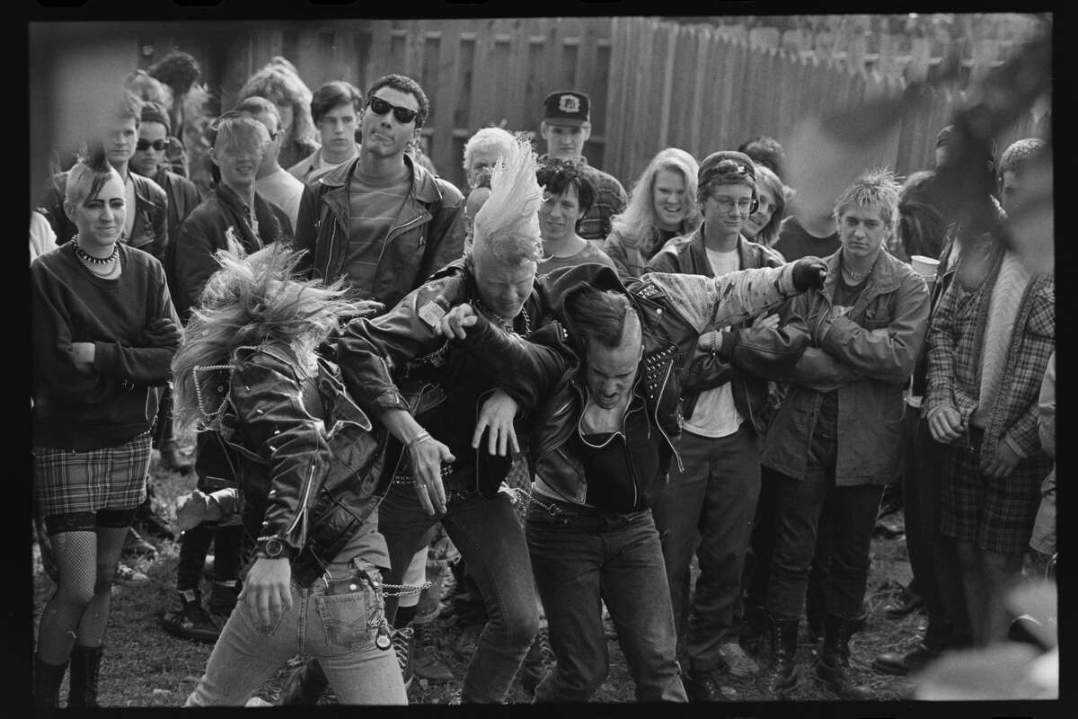 FILE - Punks in a backyard show in Oakland in 1990. Bowles was known for turning his camera toward the crowd and was excited by their unique interactions with one another.