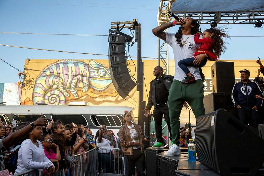 Prezi, carrying his niece, performs during the Bayview Live Music Festival as people get on stage and dance on Saturday, Oct. 26, 2019, in San Francisco, Calif. Photo: Santiago Mejia / The Chronicle