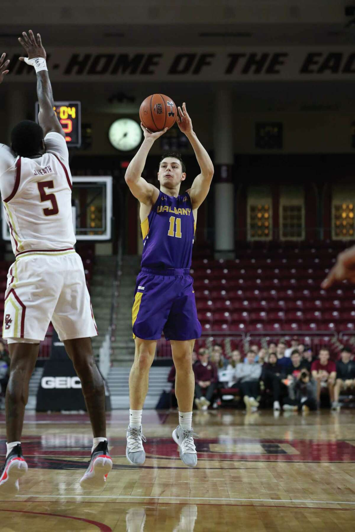 UAlbany's Cameron Healy (11) puts up a shot against Boston College's Jay Heath on Tuesday in Chestnut Hill, Mass.