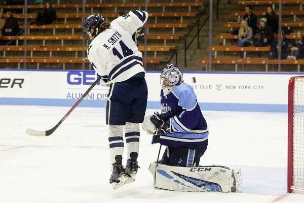 Yale's Mitchell Smith with a screen of Maine goaltender Jeremy Swayman.