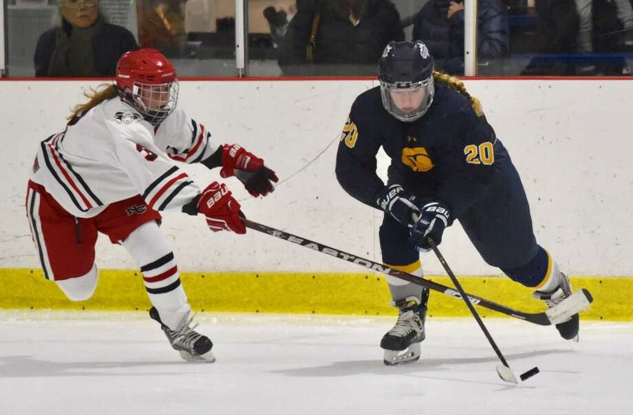 New Canaan's Courtney O'Connell (3) attempts to knock the puck away from Simsbury's Grace Melanson (20) at the Darien Ice House on Tuesday. Photo: David Stewart / Hearst Connecticut Media / Connecticut Post