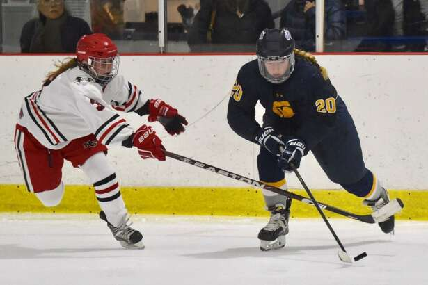 New Canaan's Courtney O'Connell (3) attempts to knock the puck away from Simsbury's Grace Melanson (20) at the Darien Ice House on Tuesday.