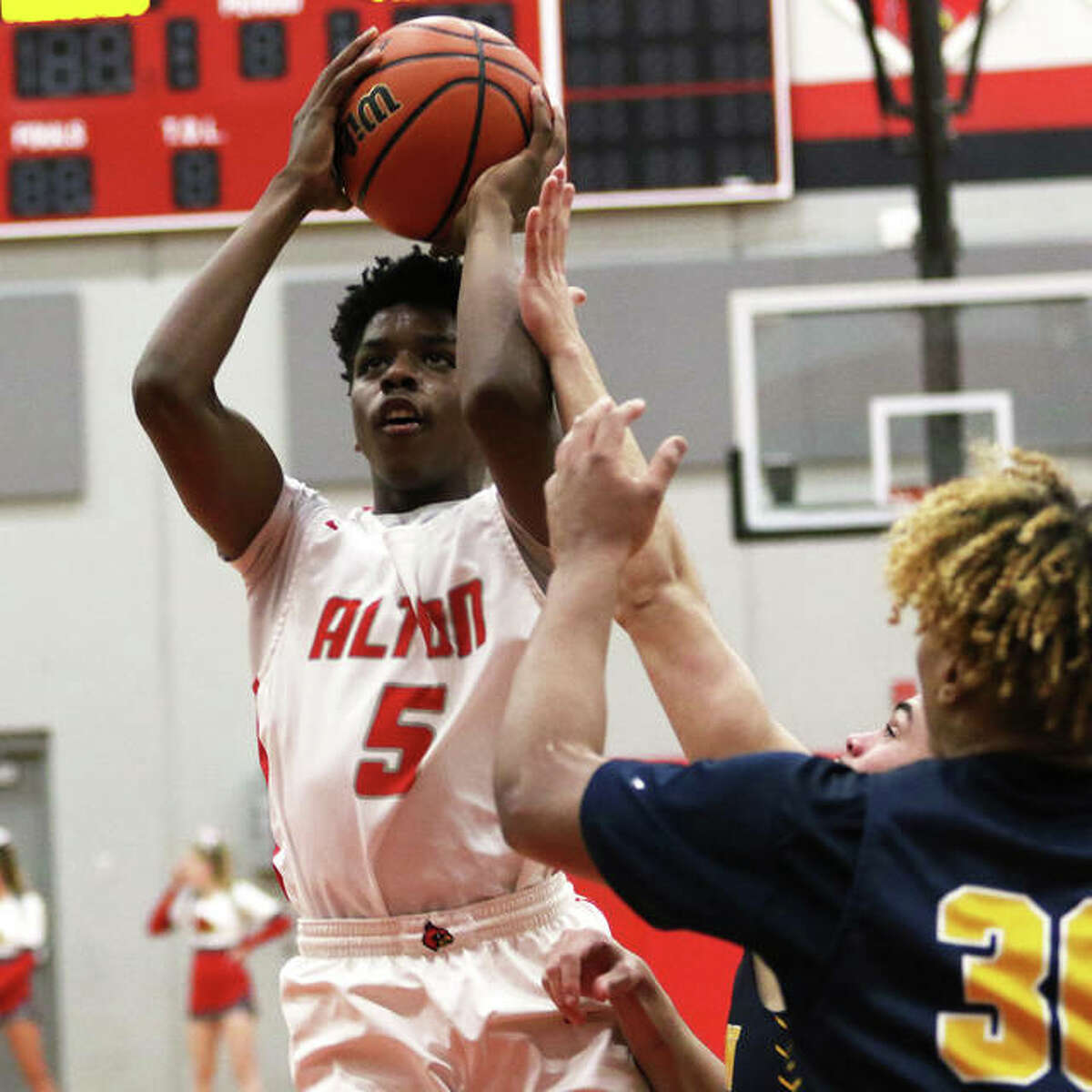 Alton's Camren Edwards (5) puts up a shot in the lane against the O'Fallon Panthers on Tuesday night in Godfrey.