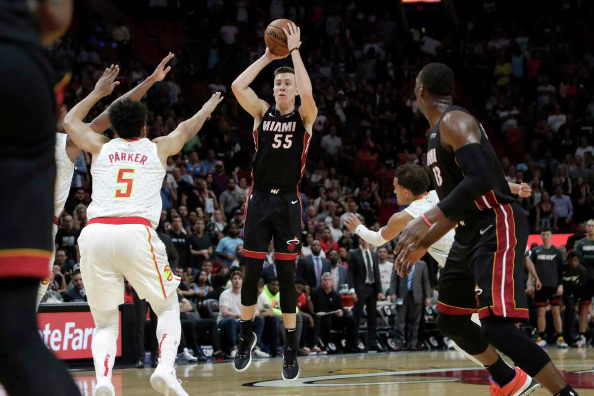 Miami Heat forward Duncan Robinson (55) shoots a 3-pointer as Atlanta Hawks forward Jabari Parker (5) defends during overtime of an NBA basketball game, Tuesday, Dec. 10, 2019, in Miami. The Heat won 135-121 in overtime. (AP Photo/Lynne Sladky)