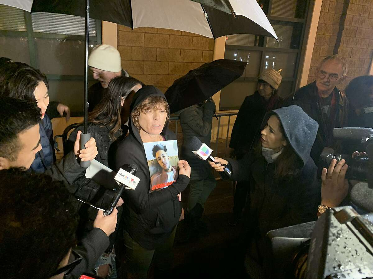 A woman, who identified herself only as the mother of the man critically shot by San Francisco police in the Missoin District, holds a photo of who she says is her son, Jamaica, 26, during a protest outside of the San Francisco Police Department's Mission Station on Tuesday, Dec. 10, 2019. She declined to provide the man's surname and did not identify herself to reporters.