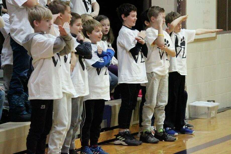 """(LEFT) Students enjoy a fun game of quickdraw in which they have to make an """"L,"""" an """"X,"""" or a salute. If they make the same sign as their leader simultaneously made, then they are out. (RIGHT) The student Fuel Up to Play 60 team encourages their classmates to stay active, even in the winter months. (Photos/Robert Myers)"""