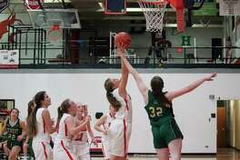 Cassidy Pallin leaps up to grab a defensive rebound for the Huskies. (Photo/Robert Myers)