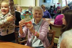 Long Hill School third graders made snow globes with residents at Wesley Village Wednesday. Third graders from the school spend time with the residents once a month.