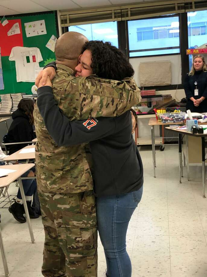 Staff Sgt. Josh Ochoa hugs his daughter Liani, 14, after he surprised her at Ridgefield High School on Tuesday, Dec. 10. He was introduced as a guest speaker in her psychology class. Photo: Stacey Gross / Contributed Photo
