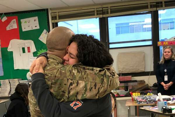 Staff Sgt. Josh Ochoa hugs his daughter Liani, 14, after he surprised her at Ridgefield High School on Tuesday, Dec. 10. He was introduced as a guest speaker in her psychology class.