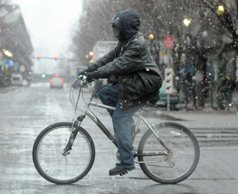 (Peter Hvizdak Ñ New Haven Register) A bicyclist navigates Chapel Street during a snowfall in New Haven Tuesday morning December 10, 2013. Photo: Peter Hvizdak / New Haven Register / ©Peter Hvizdak /  New Haven Register