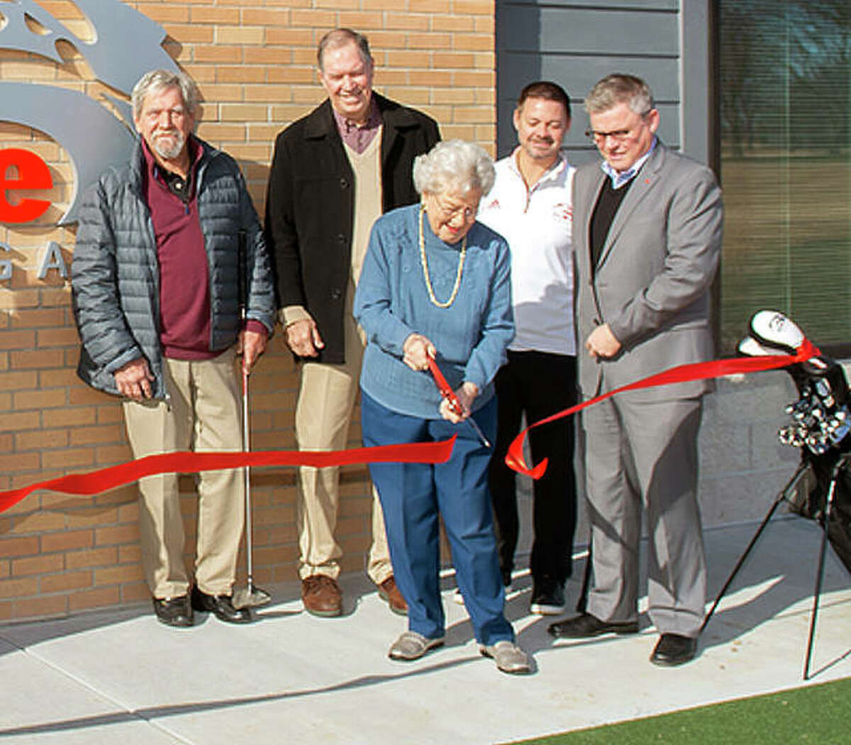 Bev Gallatin, surrounded by family and friends, cuts to ribbon to open the new Harry Gallatin SIUE Golf Practice Facility Tuesday at Sunset Hills Country Club, named in memory of her late husband, who was a longtime golf and basketball coach at SIUE.