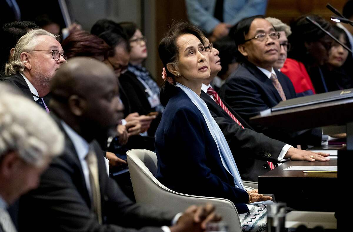 """TOPSHOT - Myanmar's State Counsellor Aung San Suu Kyi (C) stands before the UN's International Court of Justice on December 11, 2019 next to Abubacarr Tambadou (2L), minister of justice of the Gambia, in the Peace Palace of The Hague, on the second day of her hearing on the Rohingya genocide case. - Aung San Suu Kyi appears at the UN's top court today, a day after the former democracy icon was urged to """"stop the genocide"""" against Rohingya Muslims. Once hailed internationally for her defiance of Myanmar's junta, the Nobel peace laureate will this time be on the side of the southeast Asian nation's military when she takes the stand at the International Court of Justice. ("""