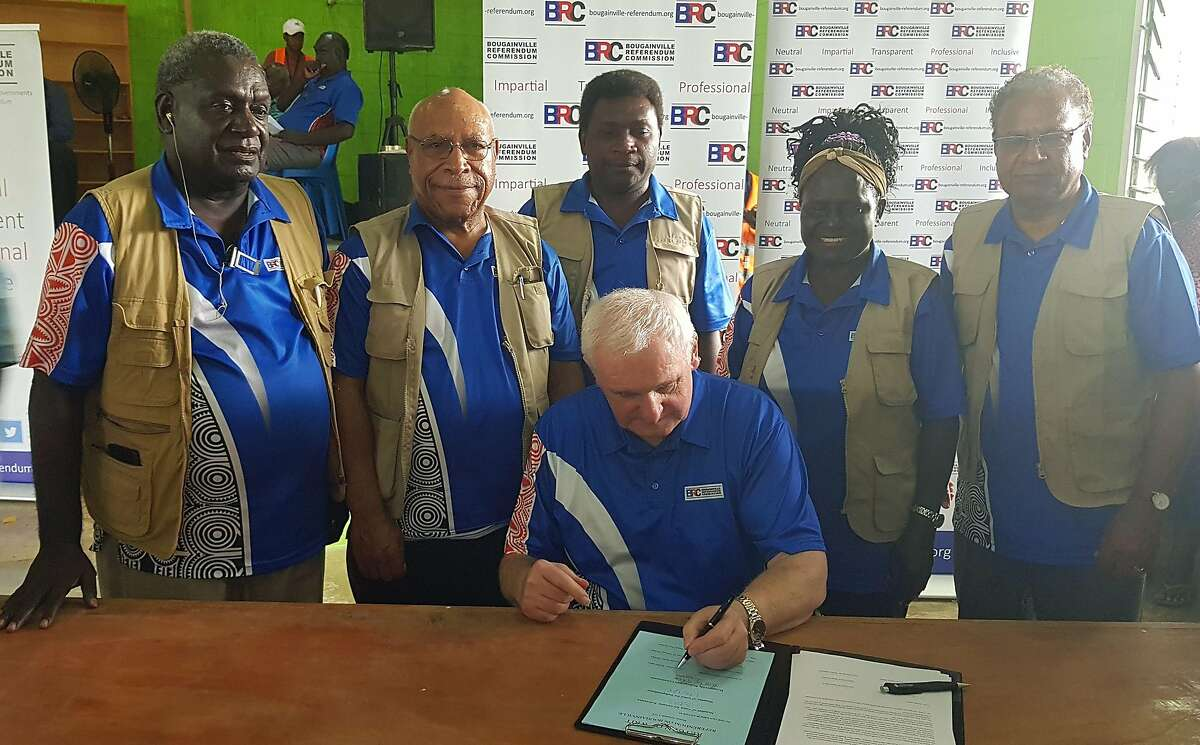 Bougainville Referendum Commission Chairman Bertie Ahern (C) signs the referendum announcement in Bougainville on December 11, 2019. - Voters backing Bougainville's independence from Papua New Guinea have won a landslide referendum victory, according to results released on December 11 -- a major step toward the troubled isles becoming the world's newest nation.