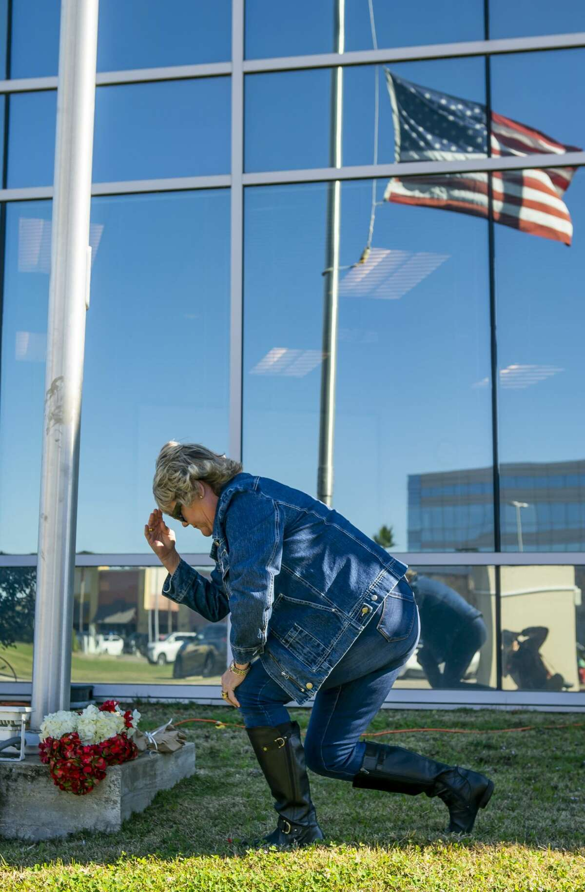 Robin Cortinas, of Taylor Lake, crosses herself after laying flowers at the American Flag at half staff in front of the building that houses the Nassau Bay City Hall and police department, Wednesday, Dec. 11, 2019. Nassau Bay Police Department Sgt. Kaila Sullivan was struck and killed by a car Tuesday night while trying to arrest a suspect. Law enforcement officials are currently searching for the suspect, 21-year-old Tavores Dewayne Henderson, who is now charged with felony murder.