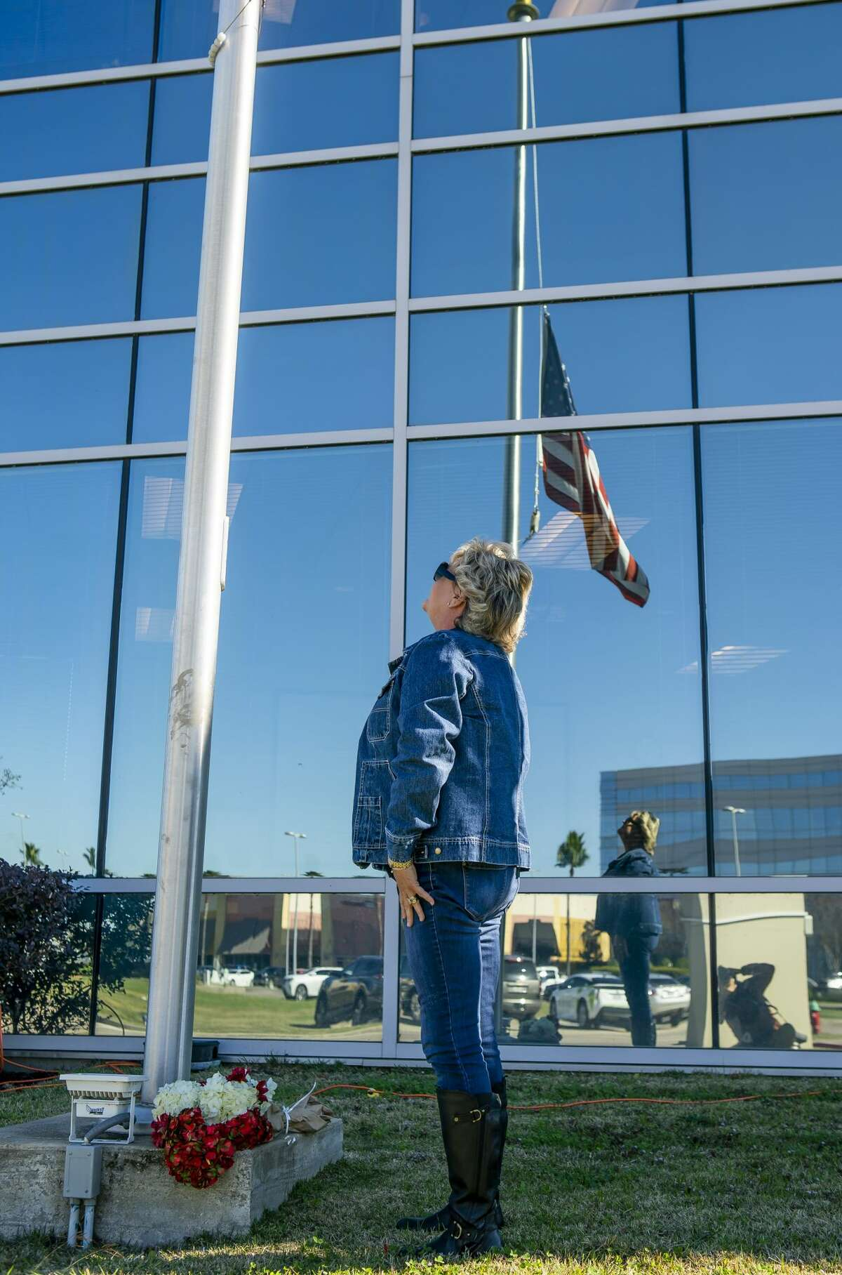 Robin Cortinas, of Taylor Lake, lays flowers at the American Flag at half staff in front of the building that houses the Nassau Bay City Hall and police department, Wednesday, Dec. 11, 2019. Nassau Bay Police Department Sgt. Kaila Sullivan was struck and killed by a car Tuesday night while trying to arrest a suspect. Law enforcement officials are currently searching for the suspect, 21-year-old Tavores Dewayne Henderson, who is now charged with felony murder.