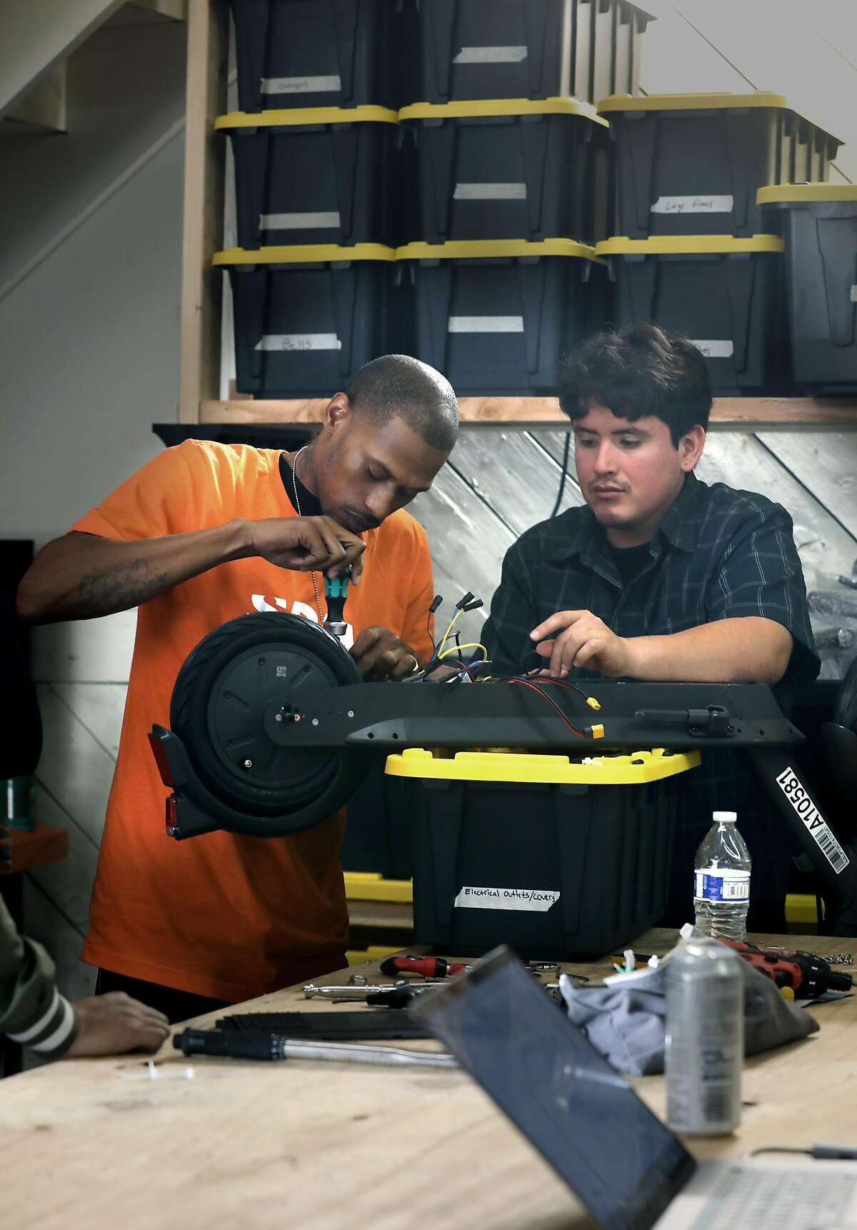 Mechanic Oscar Henriquez (right) teaches mechanic Shamar Bell (left) scooter maintenance at the Spin warehouse on Monday, Oct. 14, 2019, in San Francisco, Calif.
