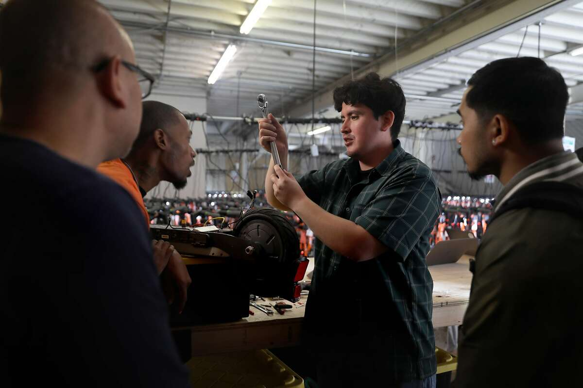 Mechanic Oscar Henriquez (middle right) teaches scooter maintenance to other mechanics at the Spin warehouse on Monday, Oct. 14, 2019, in San Francisco, Calif.