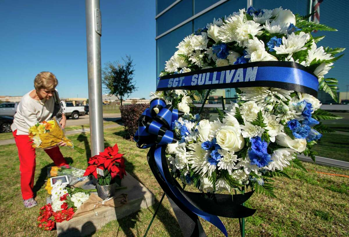 Sally Wittington, who has lived in the area for over thirty years, lays flowers at the American Flag at half staff in front of the building that houses the Nassau Bay City Hall and police department, Wednesday, Dec. 11, 2019. Nassau Bay police officers patrol Wittington's neighborhood, and she said she was up late last night listening to the helicopters flying over the crime scene. Nassau Bay Police Department Sgt. Kaila Sullivan was struck and killed by a car Tuesday night while trying to arrest a suspect. Law enforcement officials are currently searching for the suspect, 21-year-old Tavores Dewayne Henderson, who is now charged with felony murder.