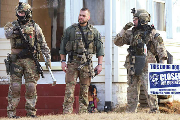 "ILEAS members, heavily armed, stand in the front yard after police posted a sign in the front yard declaring the ""Drug house closed for business."""