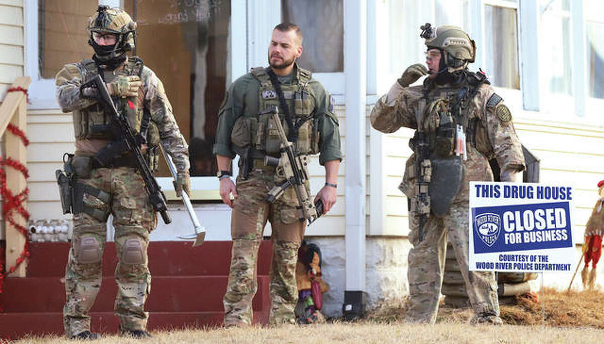 ILEAS members, heavily armed, stand in the front yard after police posted a sign in the front yard declaring the