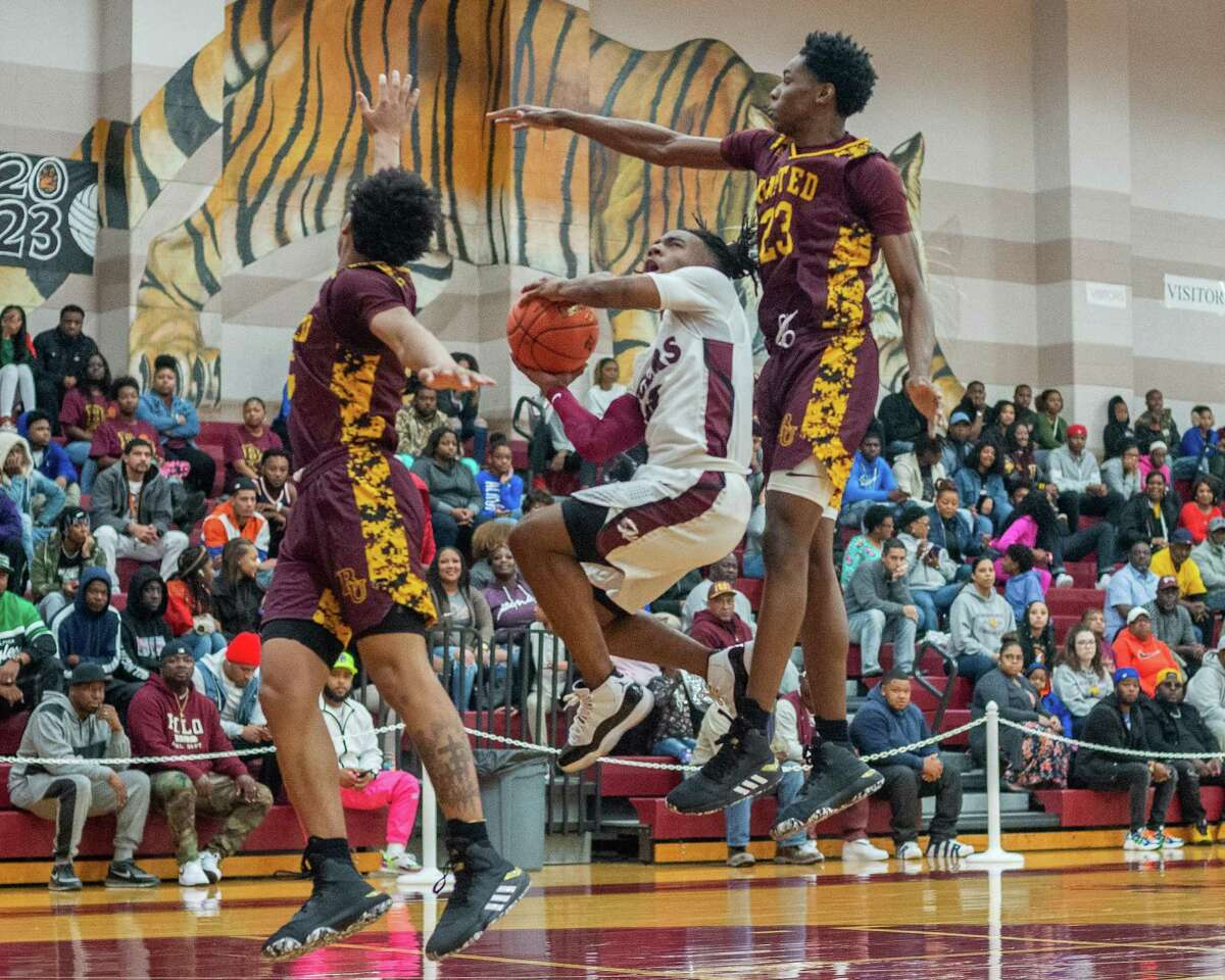 Silsbee's Jorden Edwards is defended by Beaumont United's Kaden Harrison and Terrance Arceneaux in the third quarter of their game Tuesday night. Fran Ruchalski/The Enterprise