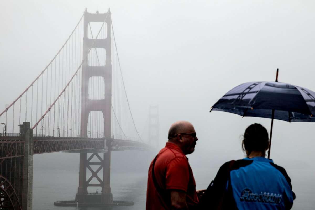 A tourist sports a Golden Gate Bridge-themed umbrella while standing on a vista overlook of the Golden Gate Bridge as rain falls in San Francisco, Calif. Wednesday, Dec. 11, 2019.
