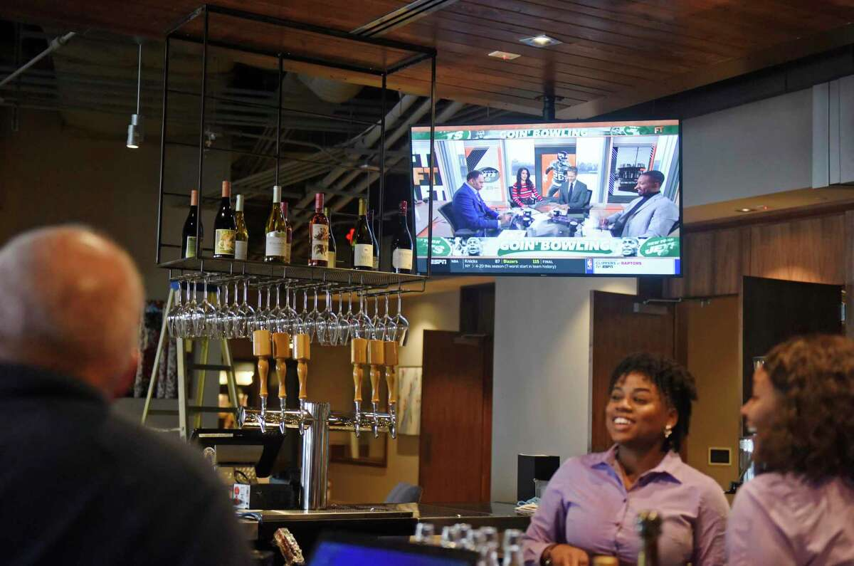 Sports are shown at the bar inside the new Pinstripes bistro, bowling, and bocce lounge at the SoNo Collection shopping center in South Norwalk, Conn. Wednesday, Dec. 11, 2019. The cavernous complex includes 12 bowling lanes, three bocce courts, full-service bar, restaurant and patio space. Pinstripes is the first restaurant to open on the concourses of the new Norwalk mall with more than a dozen expected.
