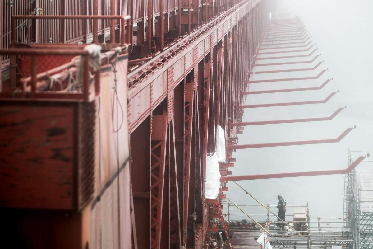 A construction worker stands on scaffolding while working to install large struts used as part of a planned suicide net sit underneath the east side of the Golden Gate Bridge in San Francisco, Calif. Wednesday, Dec. 11, 2019.
