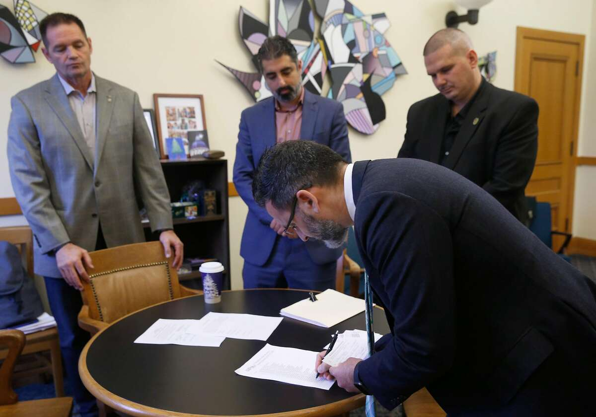 Teamsters Local #665 representative Joe Matekel (left), Spin Scooter senior policy counsel Nima Rahimi (center) and Teamsters Local #665 president Tony Delorio (right) observe Supervisor Ahsha Safai verifying union cards signed by Spin employees who voted to join the union in San Francisco, Calif. on Wednesday, Dec. 11, 2019. Spin becomes the first scooter company in the nation to have a unionized workforce.