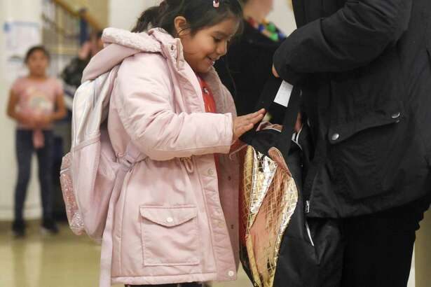 Greenwich second-grader Nicole Leon excitedly examines her new backpack at he Filling in the Blanks backpack distribution event at the Boys & Girls Club of Greenwich in Greenwich, Conn. Tuesday, Dec. 10, 2019. The Norwalk-based nonprofit Filling in the Blanks distributed backpacks containing winter hats, gloves, socks, pancake mix, toys, books, and dental items to 100 low-income club members.
