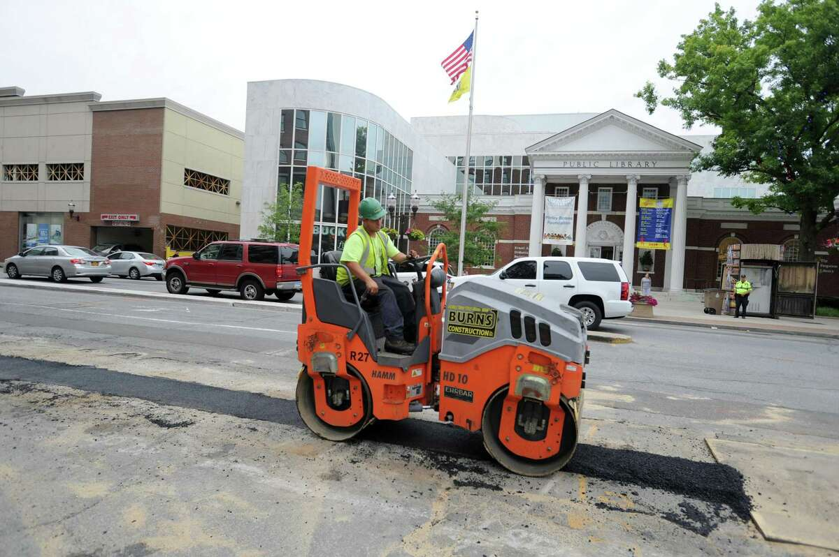 Eversource employees pave the corner of Broad St. and Bedford St. after replacing gas lines in Stamford on June 27, 2018.