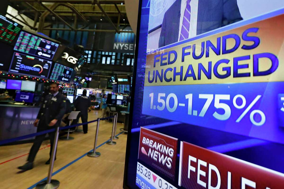 A television screen on the floor of the New York Stock Exchange shows the rate decision of the Federal Reserve, Wednesday, Dec. 11, 2019. The Federal Reserve is leaving its benchmark interest rate alone and signaling that it expects to keep low rates unchanged through next year. (AP Photo/Richard Drew)