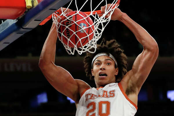 Texas forward Jericho Sims (20) dunks during the first round of the 2K Empire Classic college basketball tournament against Georgetown, Thursday, Nov. 21, 2019, in New York. (AP Photo/Kathy Willens)