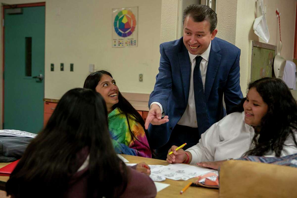SAISD Superintendent Pedro Martinez looks over student artwork as he visits a Poe Middle School art class in 2019.