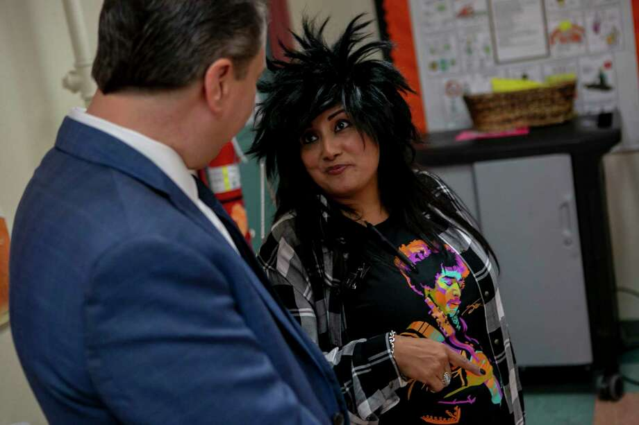 Dressed as a rocker, Poe Middle School Principal Christine Perez talks with a surprised Superintendent Martinez during his Oct. 29 visit to the school. Photo: Josie Norris / **MANDATORY CREDIT FOR PHOTOG AND SAN ANTONIO EXPRESS-NEWS/NO SALES/MAGS OUT/TV