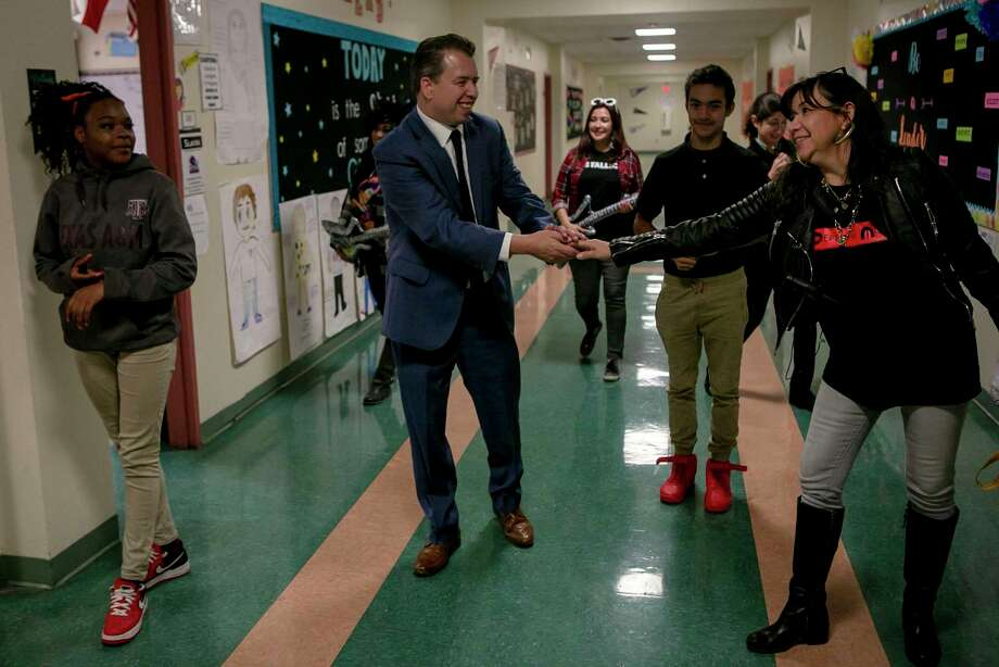 SAISD's Martinez greets a teacher in the hallway during a visit to Poe Middle School. Photo: Josie Norris /Staff Photographer / **MANDATORY CREDIT FOR PHOTOG AND SAN ANTONIO EXPRESS-NEWS/NO SALES/MAGS OUT/TV