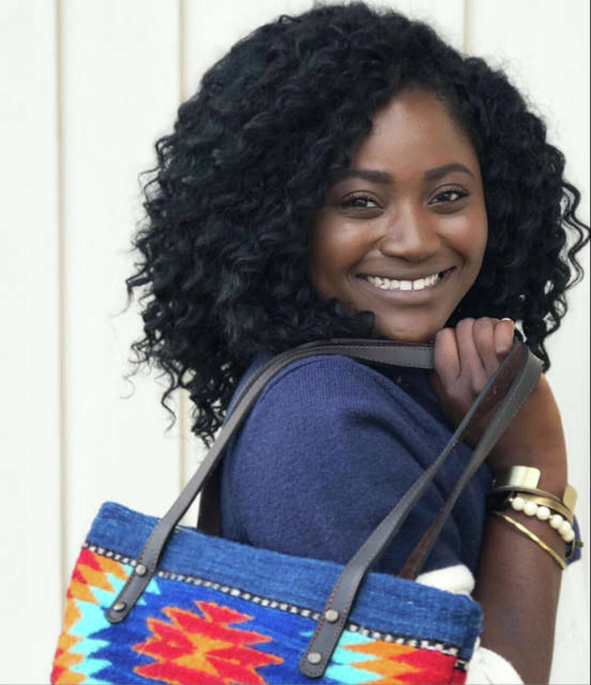 Eliana McBee, 22, a native of Haiti who lives with her husband in Godfrey, near her parents, Natalie and Michael Runyon, and nine siblings, two of whom the Runyons also adopted from Haiti, shows a bag made by a woman-owned cottage industry in Oaxaca, Mexico, and bracelets from Branded Collective, in Nashville, Tennessee, an organization that works with victims of human trafficking, and Grain of Rice Project, in Kenya. Every sale helps women business owners stay employed and out of poverty.