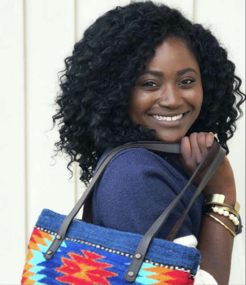 Eliana McBee, 22, a native of Haiti who lives with her husband in Godfrey, near her parents, Natalie and Michael Runyon, and nine siblings, two of whom the Runyons also adopted from Haiti, shows a bag made by a woman-owned cottage industry in Oaxaca, Mexico, and bracelets from Branded Collective, in Nashville, Tennessee, an organization that works with victims of human trafficking, and Grain of Rice Project, in Kenya. Every sale helps women business owners stay employed and out of poverty. Photo: Photo Credit American Honey Life And Photography|For The Telegraph