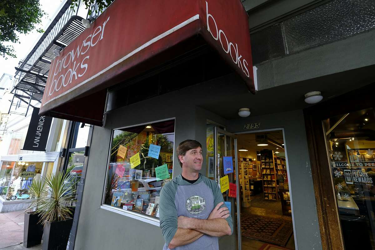 In this Wednesday, Dec. 4, 2019, photo Pete Mulvihill poses for a photo while standing outside at his Browser Books store that he recently opened in San Francisco. Mulvihill has felt optimistic enough about being an independent bookseller that he bought a third store within the past two months. (AP Photo/Eric Risberg)