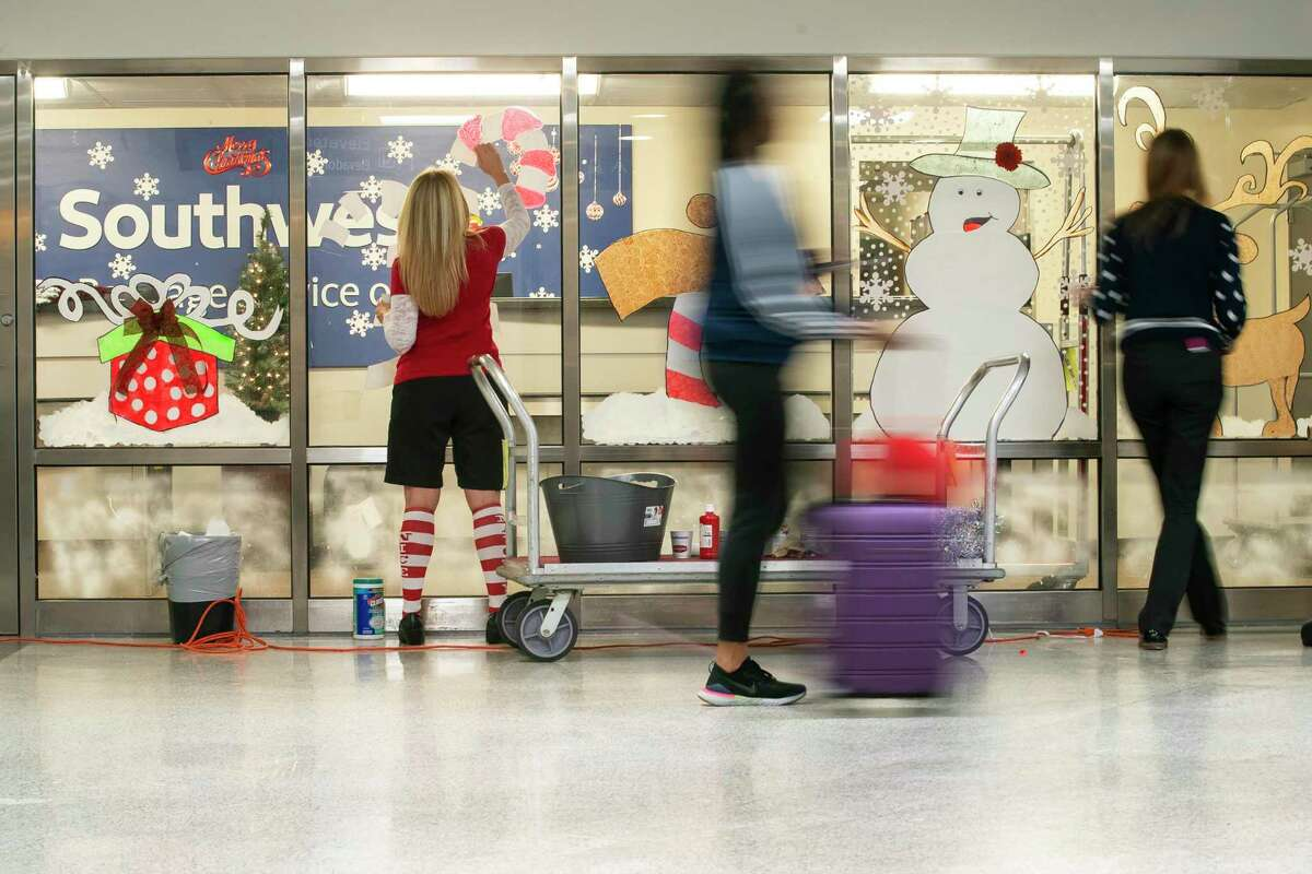 Travelers move through the baggage claim area as customer service representatives Brandi Worsham and Alicia Sumruld decorate the baggage service area at Hobby Airport in Houston, Monday, Dec. 9, 2019.