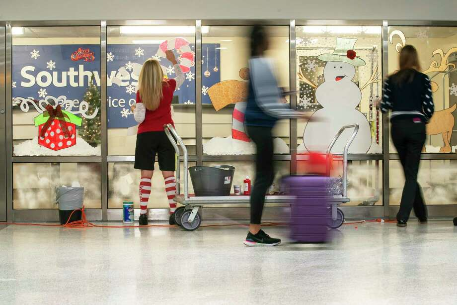 Travelers move through the baggage claim area as customer service representatives Brandi Worsham and Alicia Sumruld decorate the baggage service area at Hobby Airport in Houston, Monday, Dec. 9, 2019. Photo: Mark Mulligan, Houston Chronicle / Staff Photographer / © 2019 Mark Mulligan / Houston Chronicle