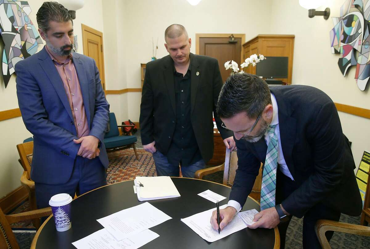Spin Scooter senior policy counsel Nima Rahimi (left) and Teamsters Local #665 president Tony Delorio (center) observe Supervisor Ahsha Safai tally union cards signed by Spin employees voting to join the union in San Francisco, Calif. on Wednesday, Dec. 11, 2019. Spin becomes the first scooter company in the nation to have a unionized workforce.