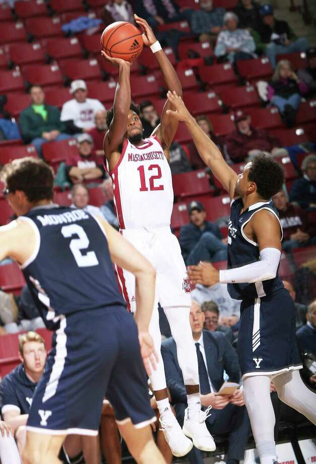 UMass' Carl Pierre (12) shoots over over Yale's Azar Swian, right, on Wednesday in Amherst, Mass. Photo: J. Anthony Roberts / Associated Press / The Republican