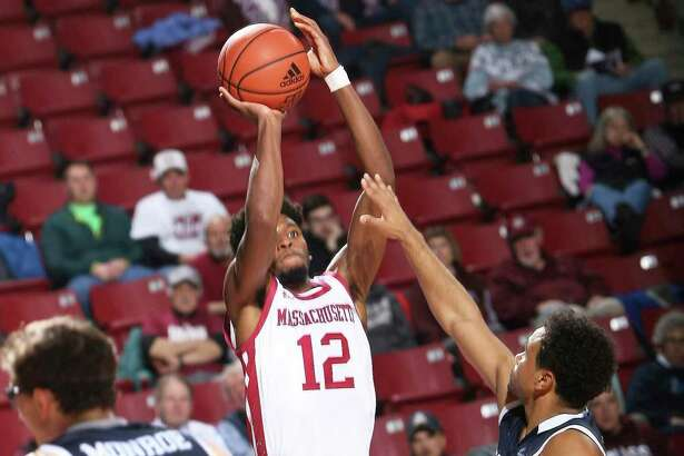 UMass' Carl Pierre (12) shoots over over Yale's Azar Swian, right, on Wednesday in Amherst, Mass.