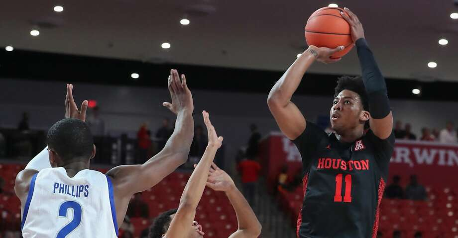 Houston Cougars guard Nate Hinton (11) gets off a shot over Texas-Arlington Mavericks forward Jordan Phillips (2) and guard Sam Griffin (1) during the first half of an NCAA basketball game at Fertitta Center Wednesday, Dec. 11, 2019, in Houston. Photo: Steve Gonzales/Staff Photographer